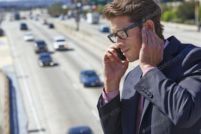 Geschäftsmann sprechen auf Handy durch laute Freeway
