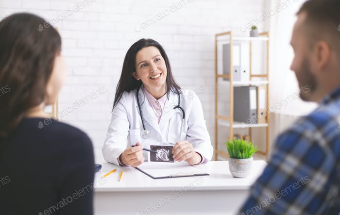 Friendly doctor explaining pregnancy diagnosis to young couple
