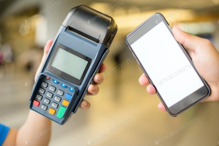 Mujer paga con teléfono móvil por tecnología NFC
