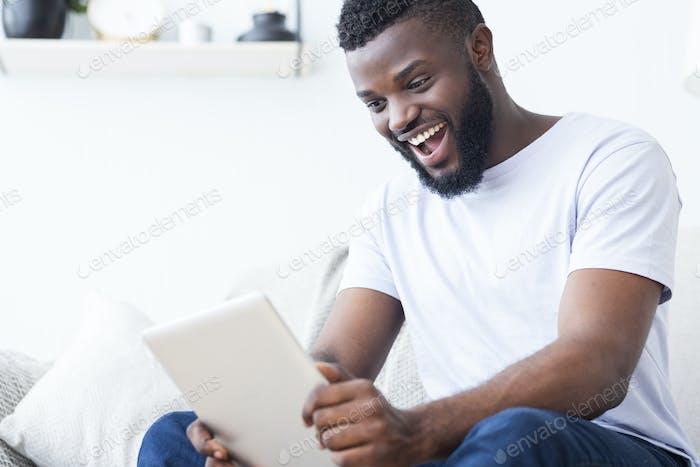 Emotionaler afrikanischer Fan beobachten Sport online auf digitalem Tablet
