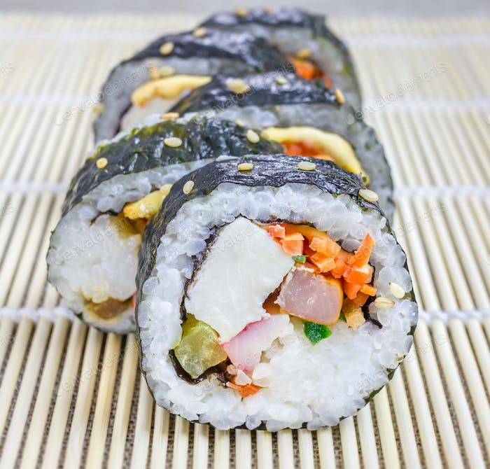 Kimbap on the bamboo mat closeup (Korean cuisine)