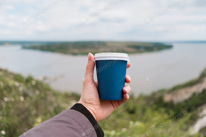 Female hand holding a Cup of Coffee to go in the morning