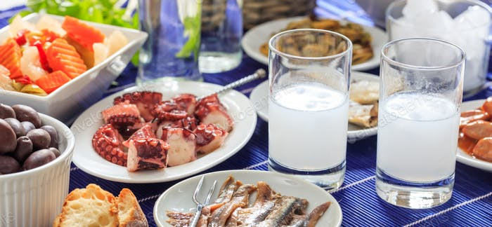 Raki glasses and seafood appetizers background, closeup view