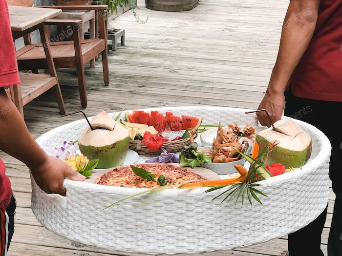 Tropical breakfast on floating tray. Fresh fruits, pineapple food and cold beverages