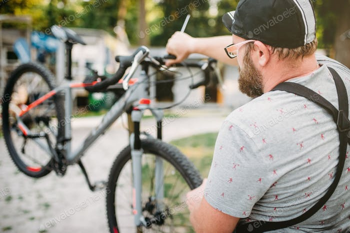 Bicycle mechanic in apron adjusts bike outdoor