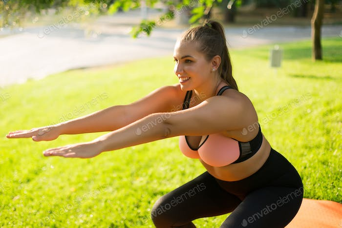 Attractive smiling plus size girl in sporty top and leggings doi