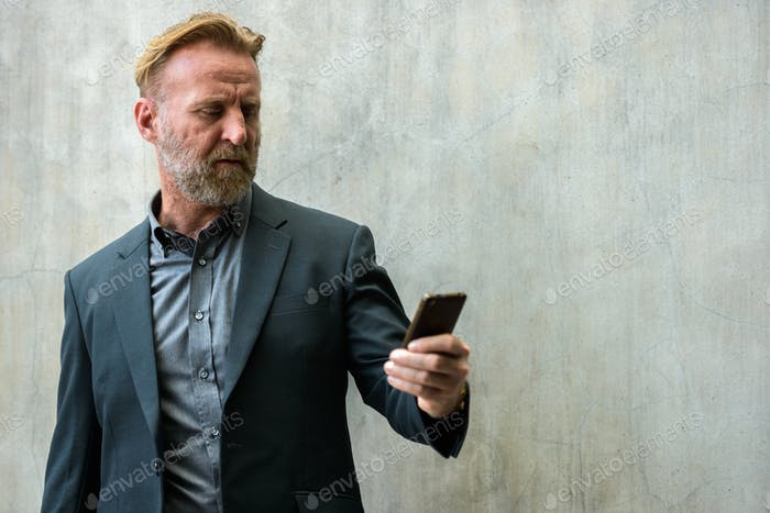 Mature handsome bearded businessman using phone outdoors