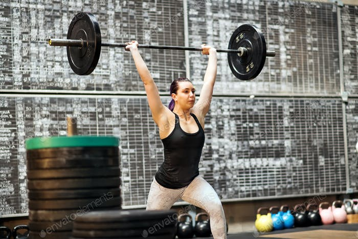 Young woman performing a clean and jerk exercise