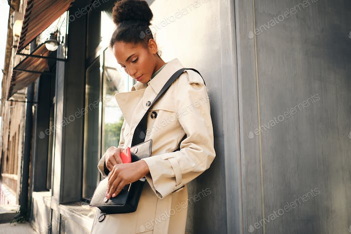 Beautiful casual African American girl in stylish trench coat taking phone out of bag outdoor