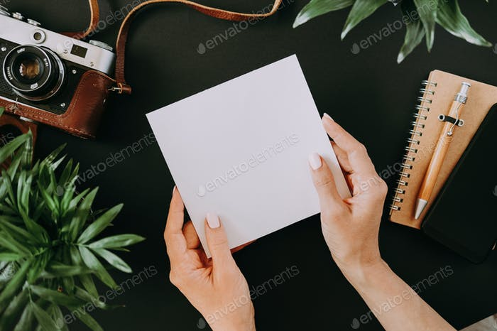 Top view of flat lay female hands holding sheet