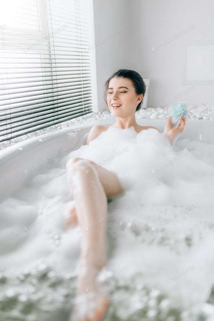 Young woman soaps the body with a sponge