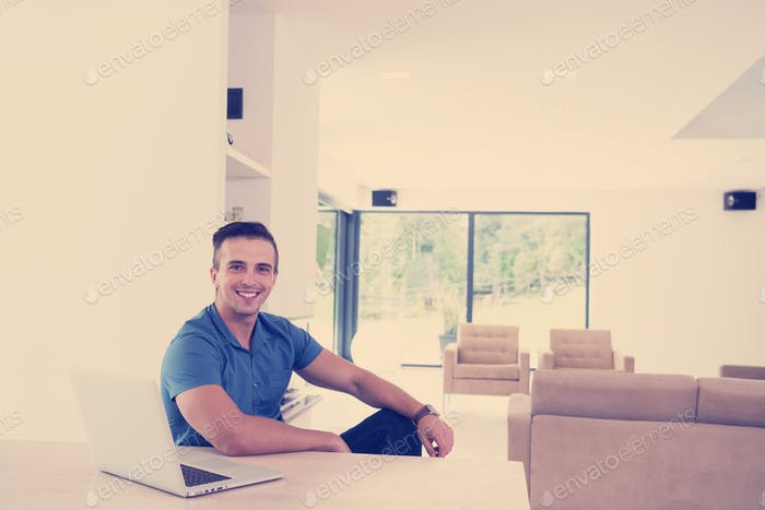 Young man with laptop at home