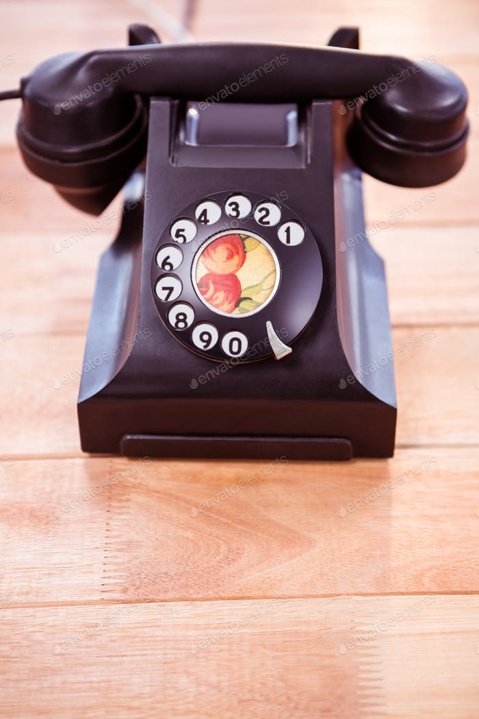 Close up view of a old phone on wooden desk