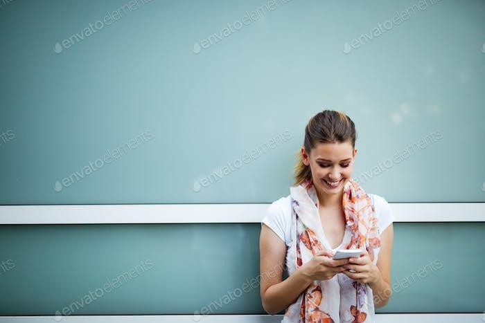 Schöne junge Frau Nachrichten auf dem Smartphone. Konzept des sozialen Netzwerks