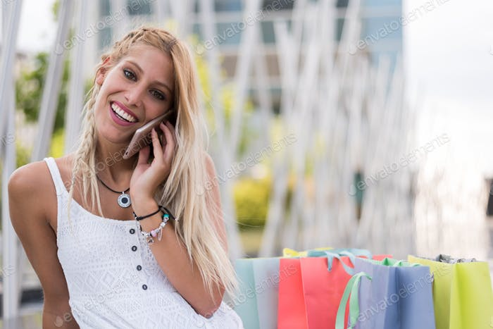 Happy blonde woman shopping and using mobile phone smiling outdoors