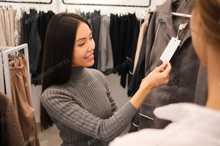 Beautiful stylish Asian girl happily choosing outfit in clothes store