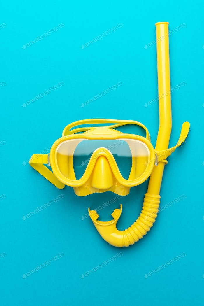 Yellow Diving Mask And Snorkel Over Blue Background With Central Composition