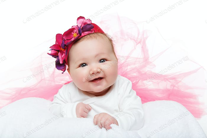 happy beautiful baby girl in tutu skirt and hat