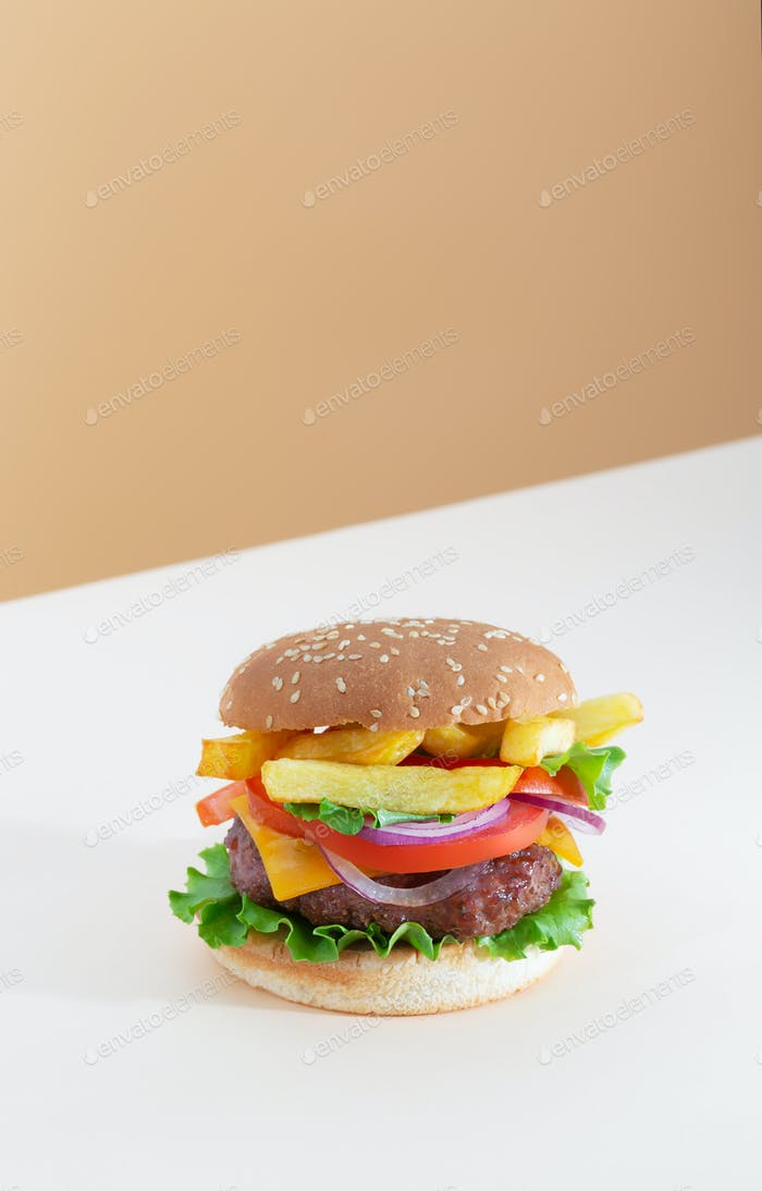 Fresh juicy beef hamburger with french fries placed on beige and brown creative trendy background