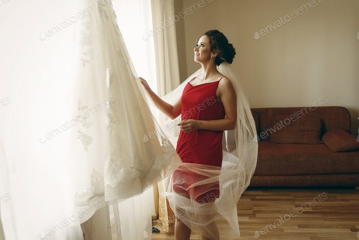 Beautiful bride in red robe with veil looking at elegant white lace wedding dress