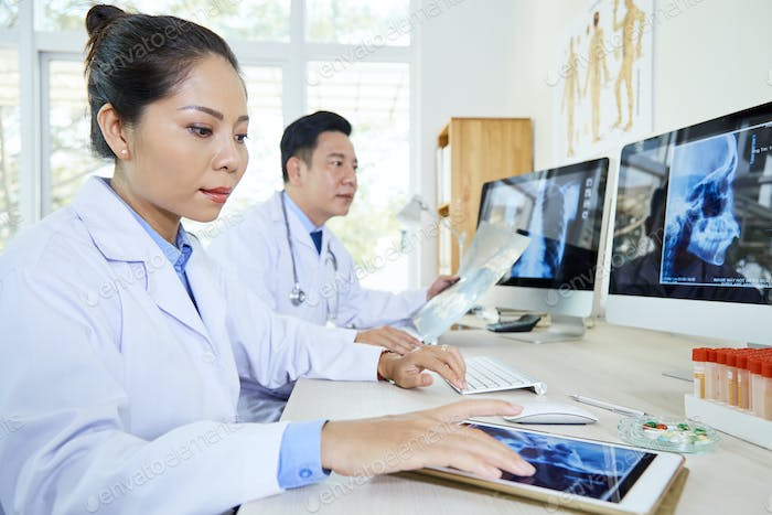 Two doctors working with x-ray images at the table at office