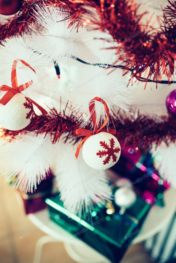 Close up on a tree decoration, a white ball with red snowflakes