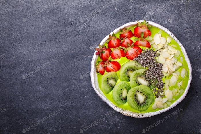Frühstück Detox Green Smoothie Bowl mit frischen Beeren, Kiwi und Chiasamen.