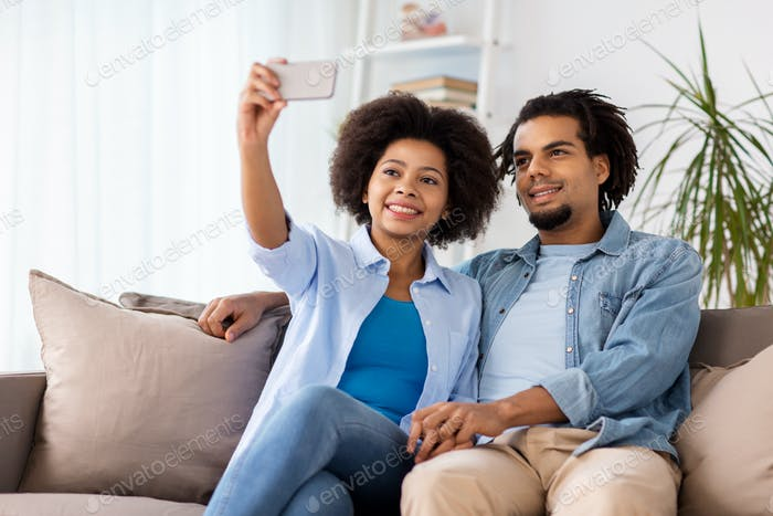 happy couple with smartphone taking selfie at home