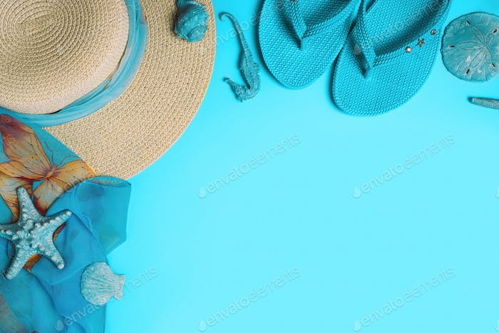 Summer fashion on blue background. Flip flops, seashells, and straw hat with scarf.