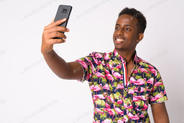 Portrait of happy young African tourist man taking selfie