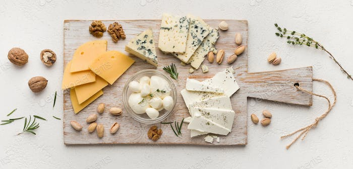 Set of cheese with nuts on wooden board
