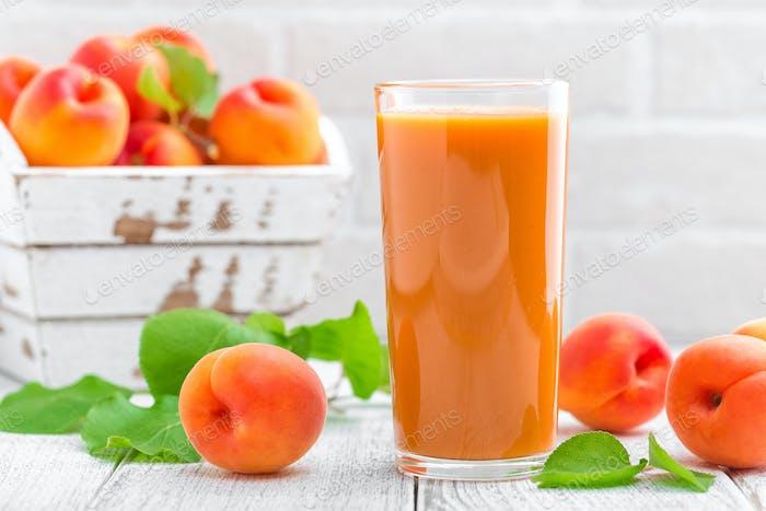 Aprikosensaft und frische Früchte mit Blättern