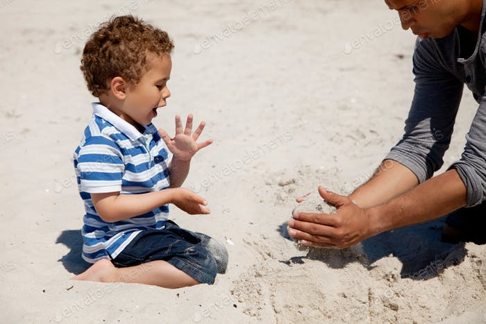 Kid Looking as His Dad Makes Sand Castle