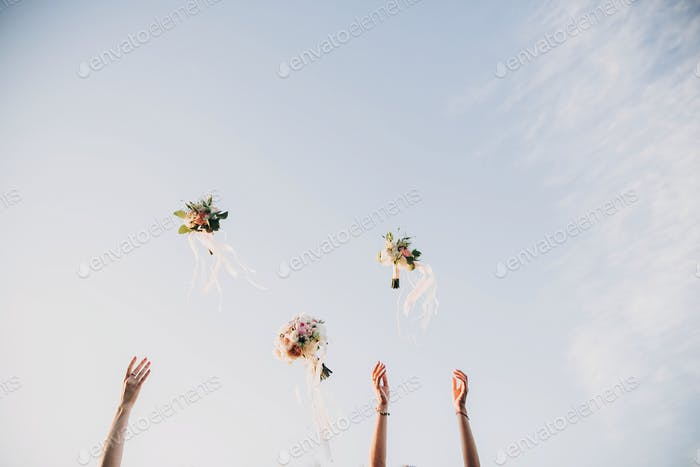 Bride and bridesmaids throwing wedding bouquets up in the sky