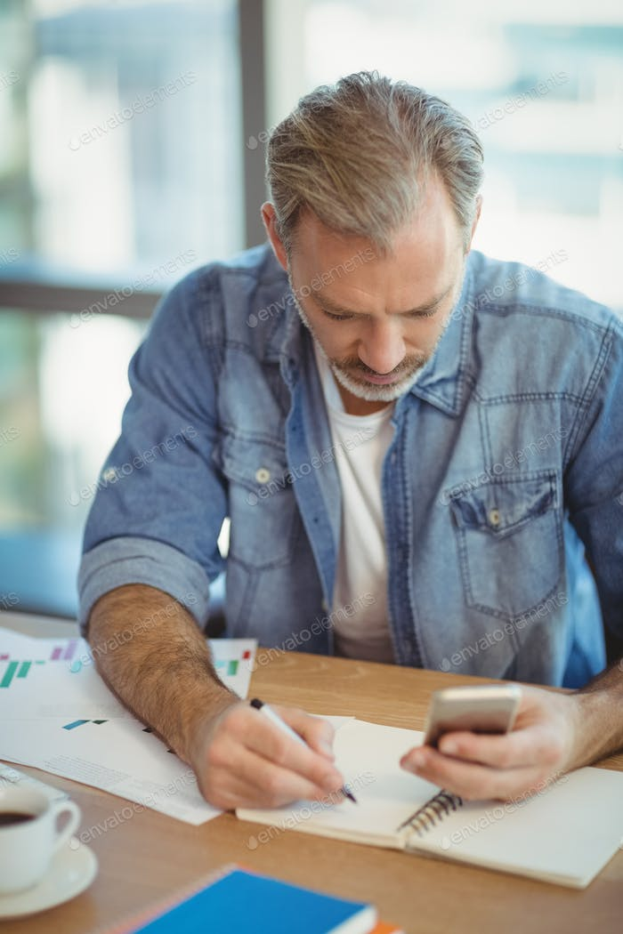 Male executive writing in organizer while using mobile phone