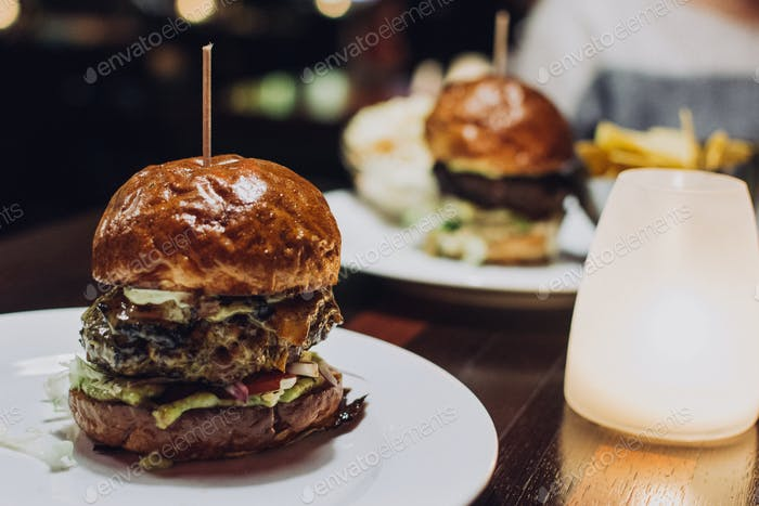Celebrating with a juicy beef burger in a restaurant