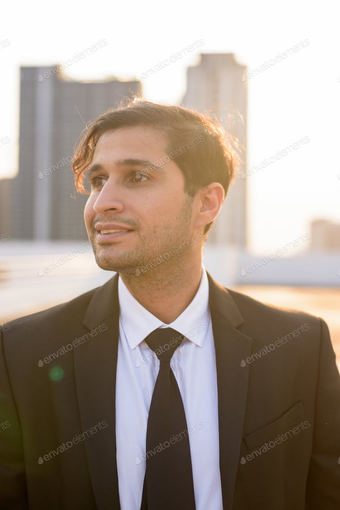 Face of happy young Persian businessman in suit thinking against view of the city