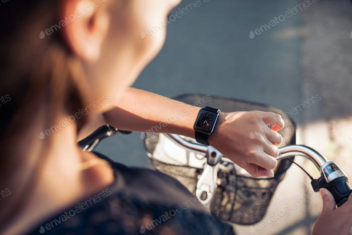 Woman with a bicycle looking at her smartwatch