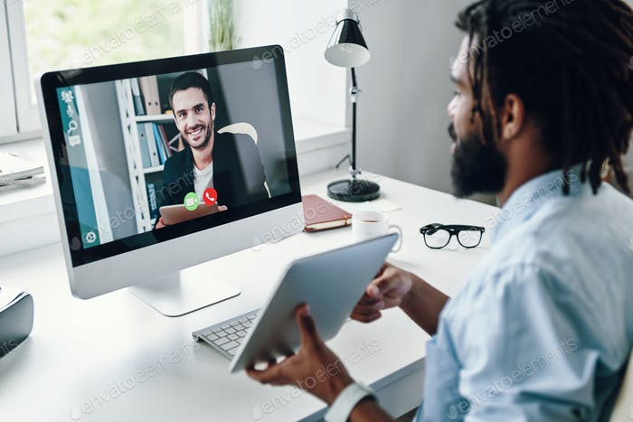 Confident young African man in shirt talking with smiling man using computer while sitting indoors