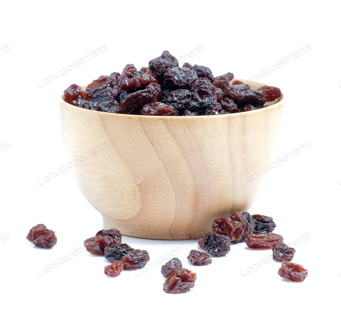 Dried grapes in wood bowl on white background.