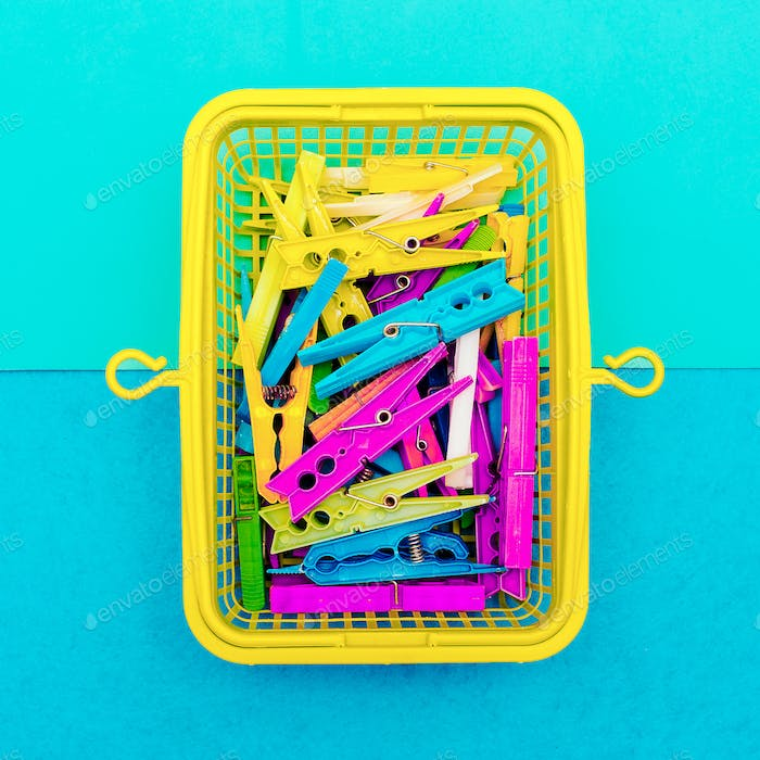 Multicolored clothespins in a basket. Minimal art style