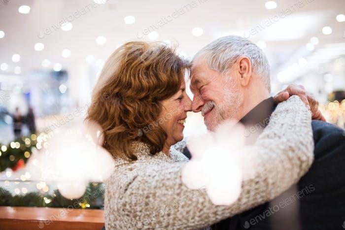 Senior couple doing Christmas shopping, hugging.