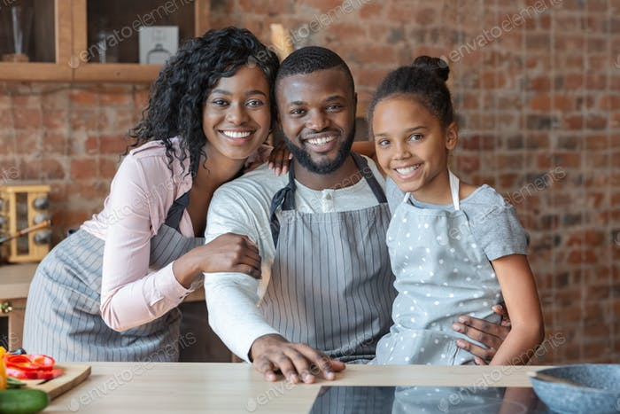 Happy family of three embracing at kitchen