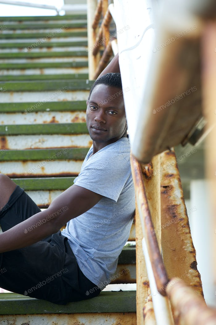 Handsome african american man sitting on stairs outdoors
