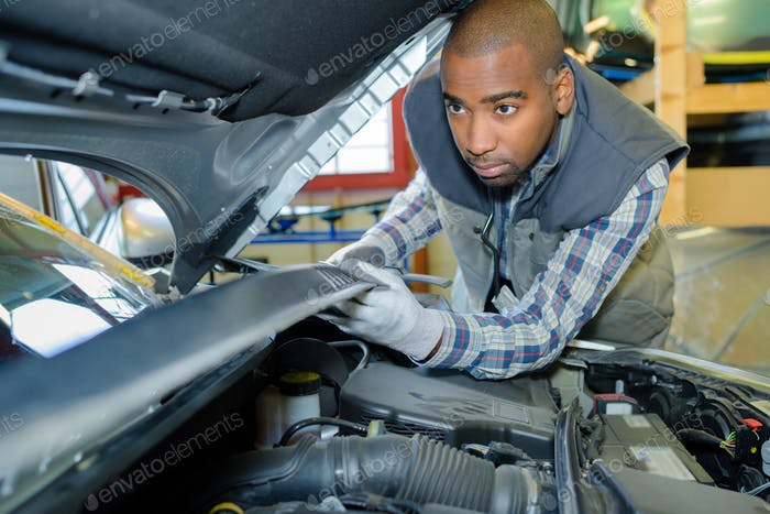 Mechanic under car bonnet