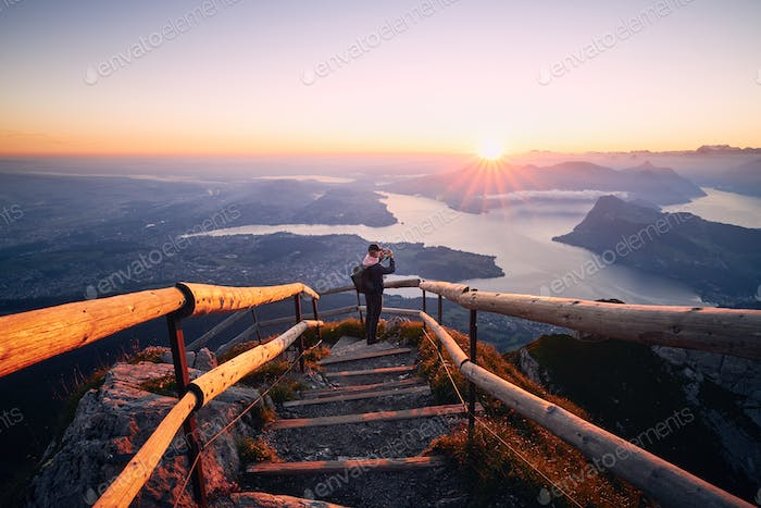 Man photographing landscape at beautiful sunrise