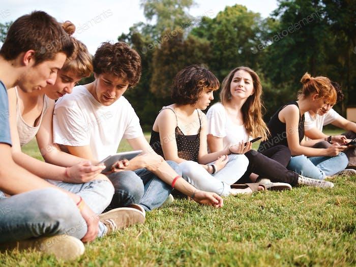 große Gruppe von Studenten, die in einem Park mit digitalen Tablets studieren