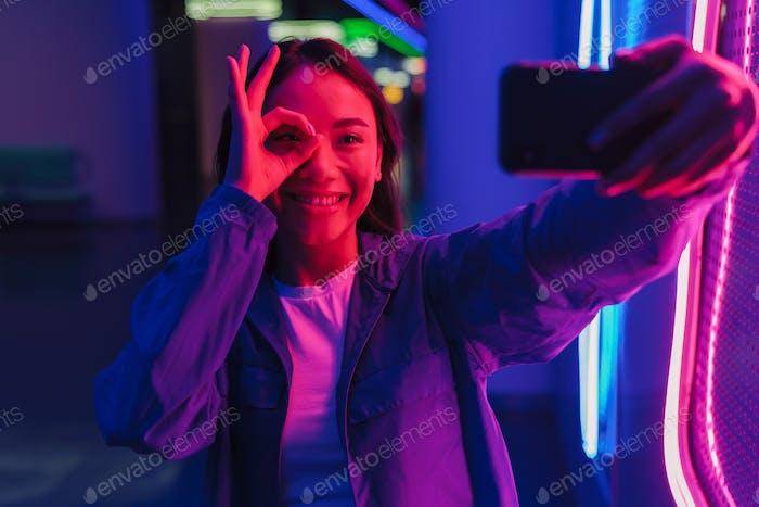Positive Frau posiert über Neonlichter.