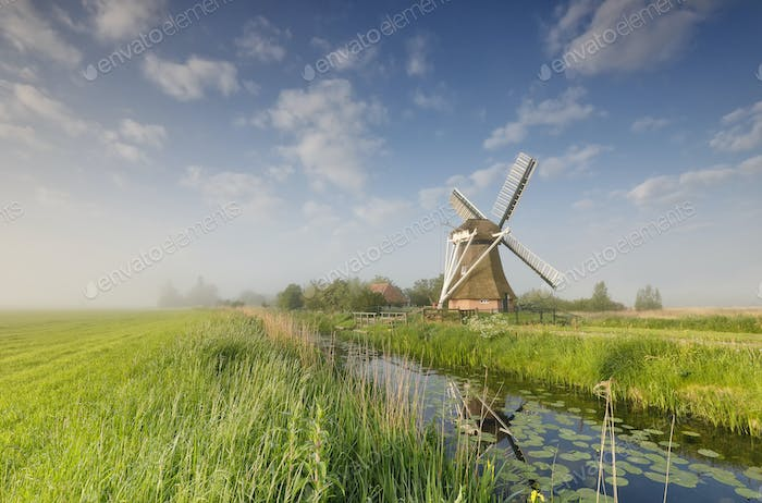 windmill on green meadow by river