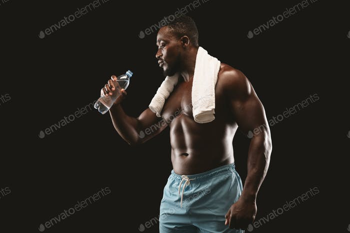 Attractive young bodybuilder drinking water during exercising